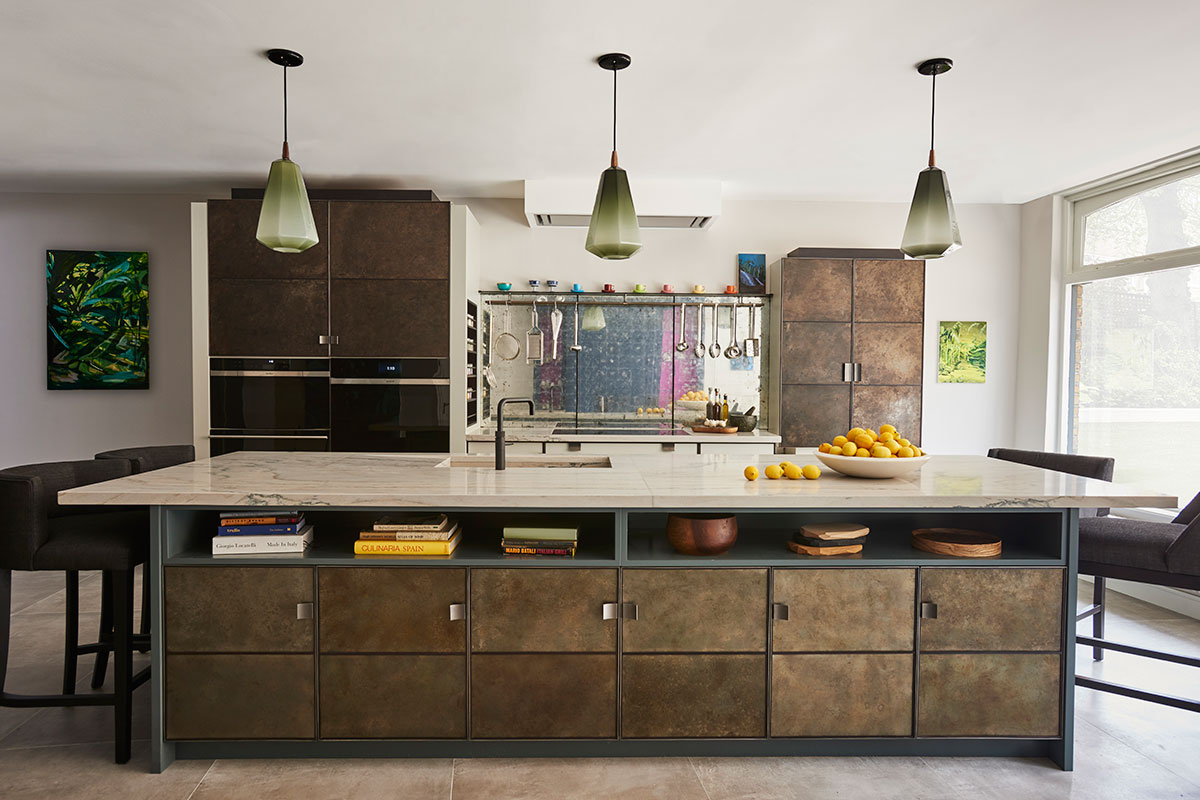 Large kitchen island with metallic doors by Ledbury Studio