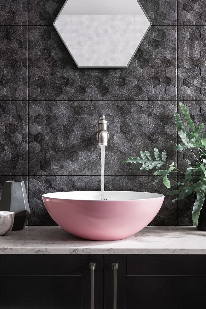 Textured black wall tiles with pink basin on marble countertop