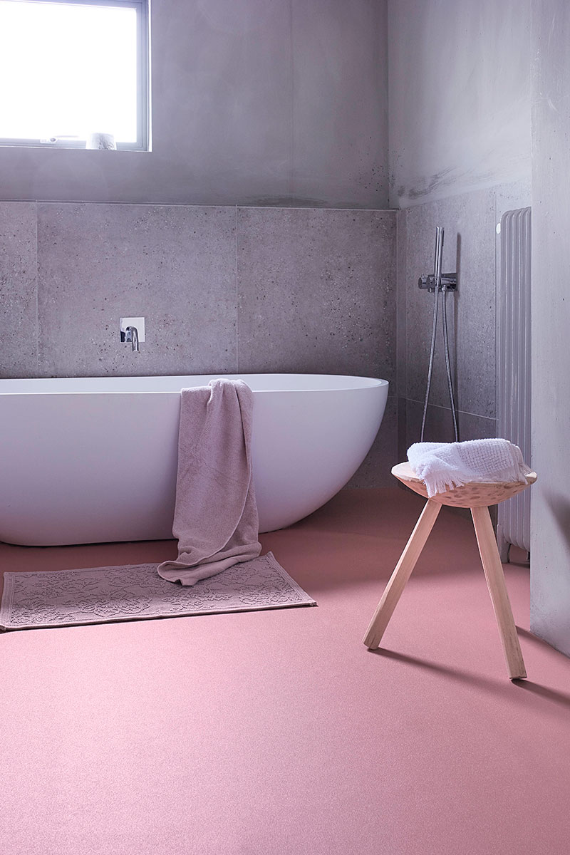 Family bathroom with pink vinyl flooring and grey cement walls