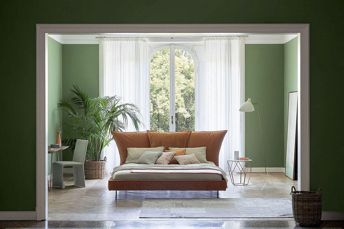 Bedroom with green walls and brown bed
