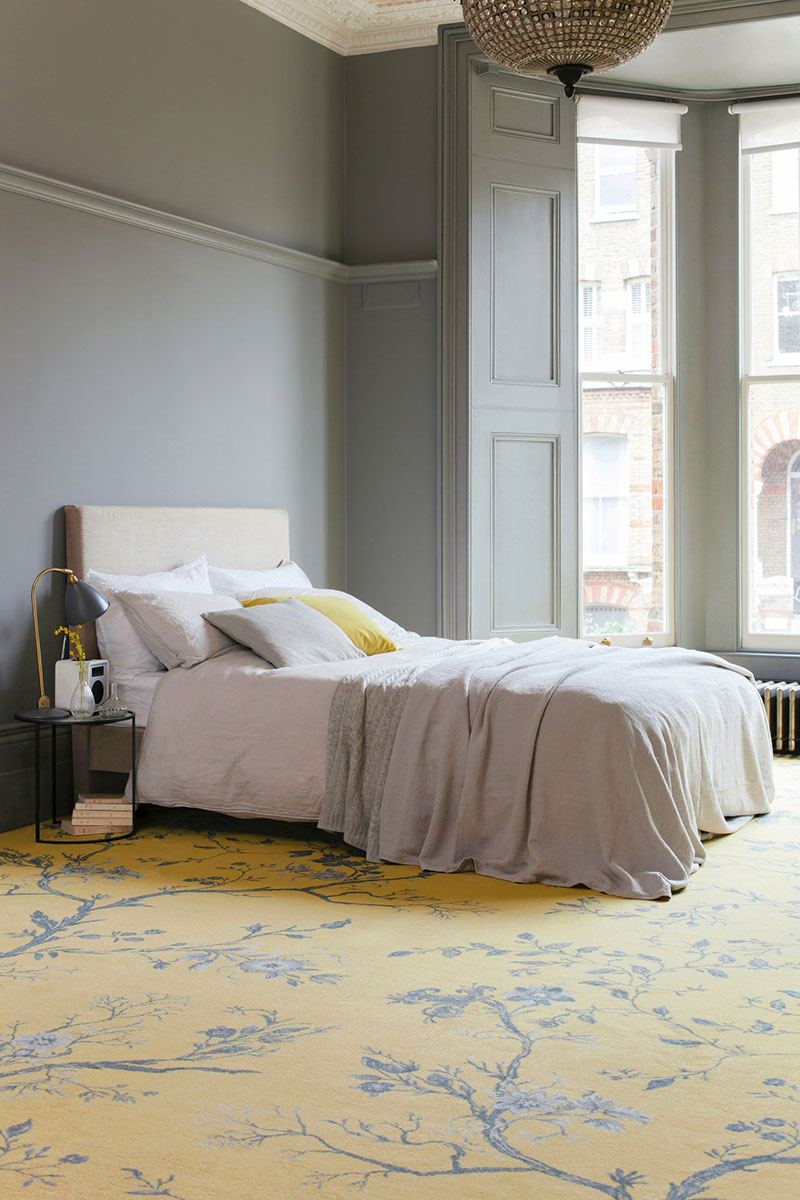 Bedroom with grey walls, neutral bed, and bright yellow patterned carpet