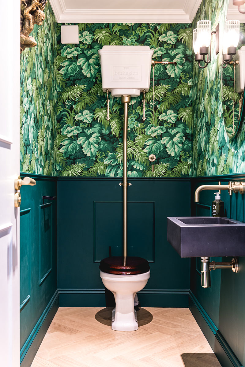 Cloakroom with tropical wallpaper and green wall cladding