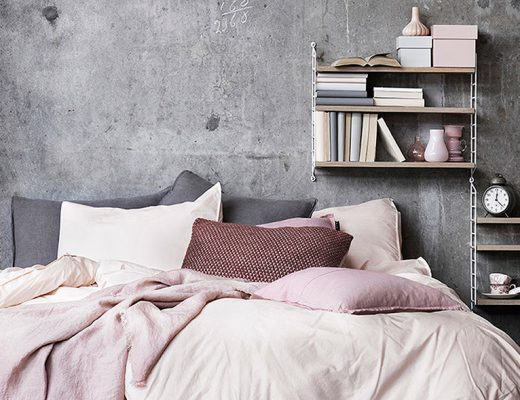 small bedroom with grey walls, pink bedding, and open shelves