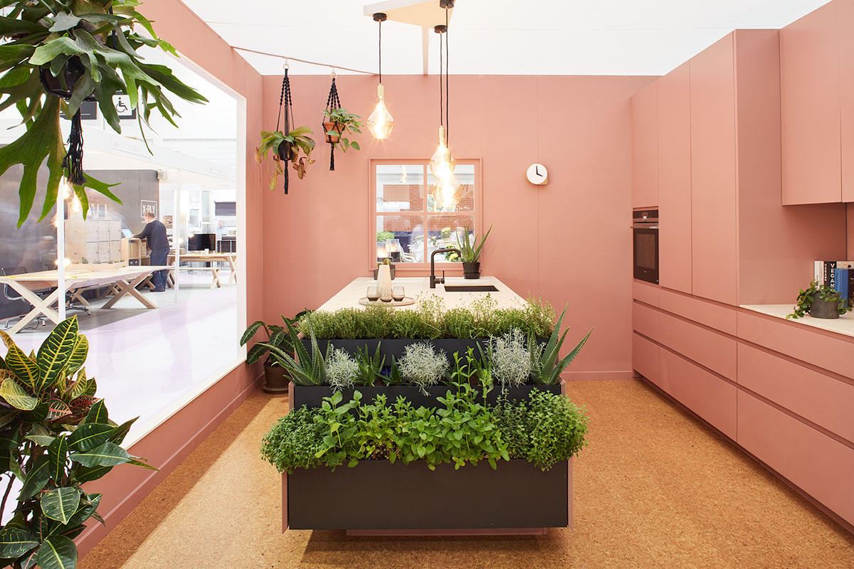 Eco-friendly kitchen in pink with island featuring planting baskets