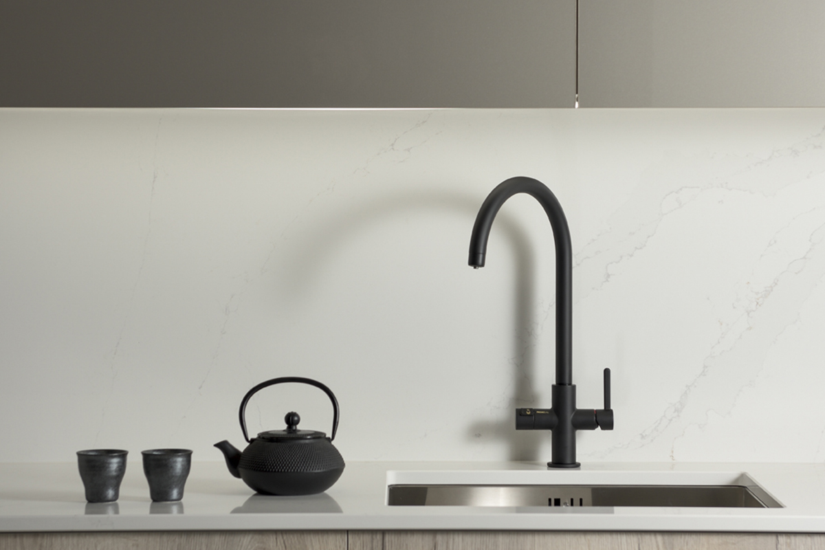 Matt black boiling-water tap with u-spout in a grey kitchen