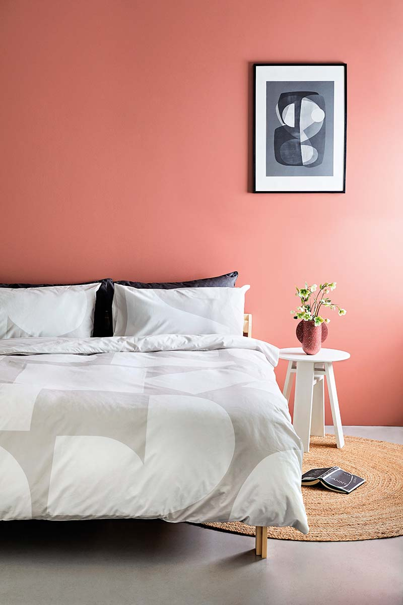 Pink wall with pared back bedding